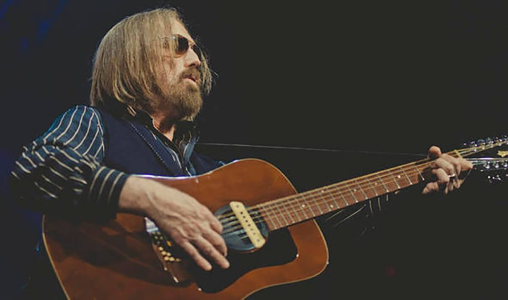 Tom Petty performs on stage, playing a guitar and singing